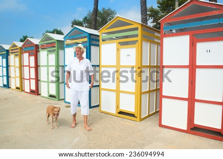 Senior man walking the dog at beach with colorful wooden huts - stock photo
