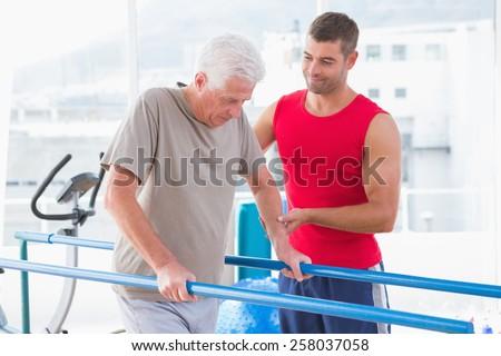 Senior man walking with coach help in fitness studio - stock photo