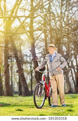 Senior man walking with his bike in park - stock photo