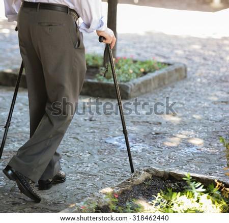 Senior man walking with wooden stick - stock photo