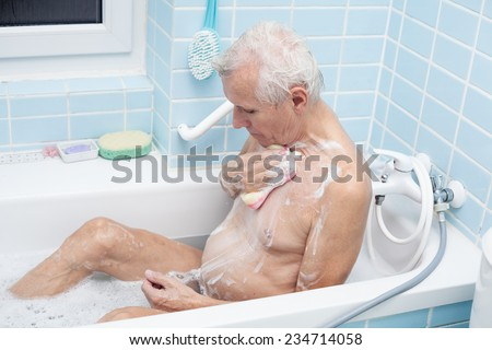Senior man washing his body with soap sponge in bath. - stock photo