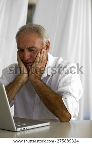 Senior man watching his laptop's screen with hands on cheeks.