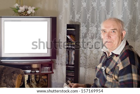 Senior man watching television with a blank white screen visible on the set as he turns to smile at the camera - stock photo