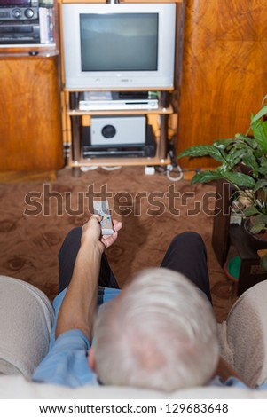 Senior man watching TV at home. Focus on remote control. - stock photo