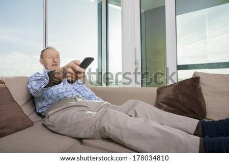 Senior man watching TV on sofa at home - stock photo