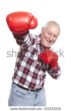 Senior man wearing boxing gloves smiling on white background - stock photo