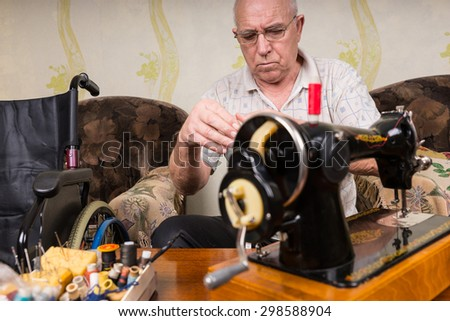 Senior Man Wearing Eyeglasses and Looking Down at Hands While Sitting in Living Room at Old Fashioned Sewing Machine