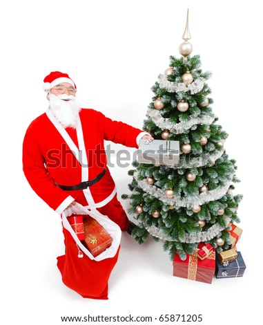 Senior man wearing Santa Claus uniform, offering present in front of Christmas tree
