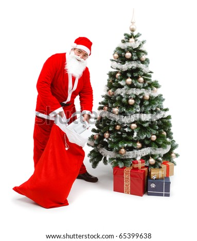 Senior man wearing Santa Claus uniform, taking out gifts from bag and putting under the decorated christmas tree