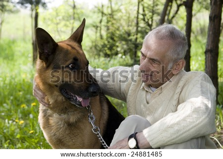Senior man who is talking with his dog in park. - stock photo