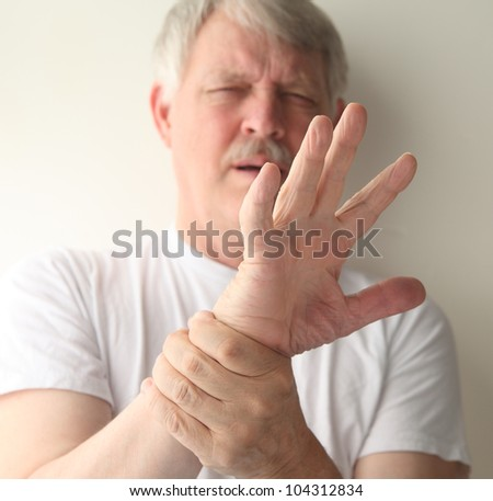 senior man winces at the pain in his hand - stock photo