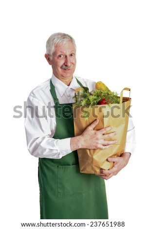 Senior man with an apron holding a bag of groceries.