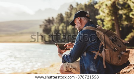 Senior man with backpack using digital tab while sitting near a lake. Mature man on hike in nature using digital tablet. - stock photo
