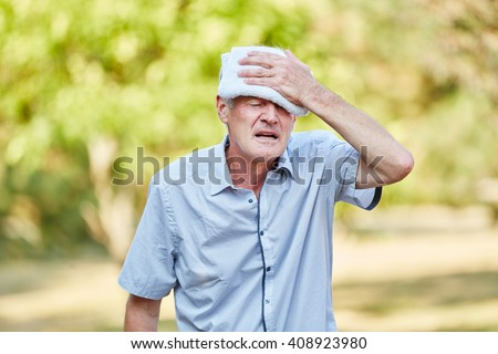 Senior man with bad circulation cools his head with wet cloth - stock photo