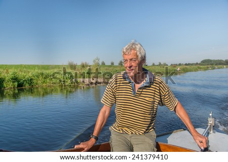 Senior man with boat at Dutch river the IJssel - stock photo