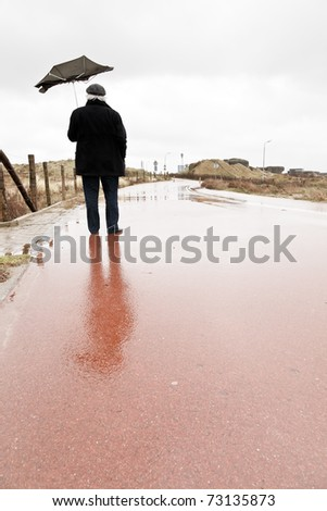 Senior man with broken umbrella by the wind standing on wet road. - stock photo