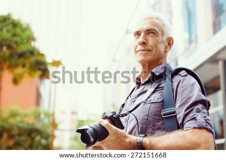 Senior man with camera in city - stock photo