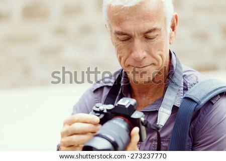 Senior man with camera in city - stock photo
