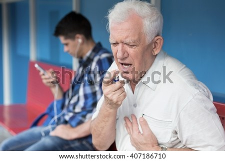 Senior man with chest pain using inhaler - stock photo