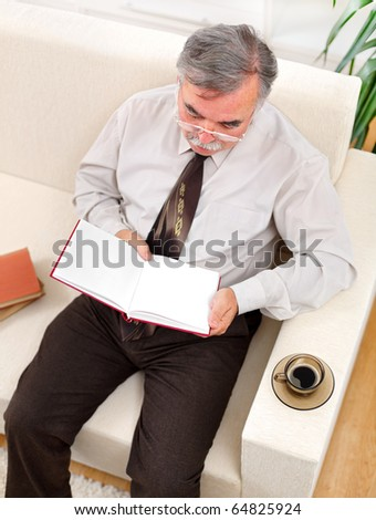Senior man with coffee, sitting on sofa and reading books