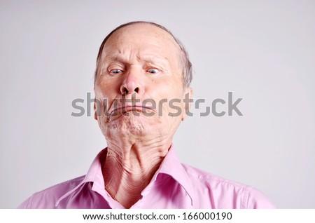 Senior man with crossed eyes  on grey background - stock photo