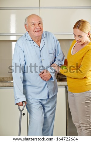 Senior man with crutches in the kitchen getting help from eldercare assistant - stock photo