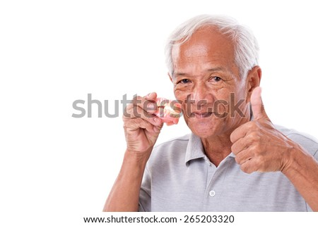 senior man with denture, giving thumb up - stock photo