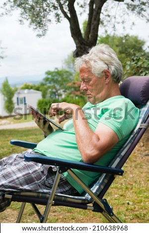 Senior man with digital tablet outdoor in nature - stock photo