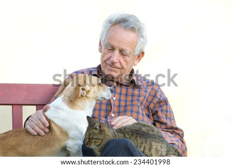 Senior man with dog and cat on his lap on bench - stock photo