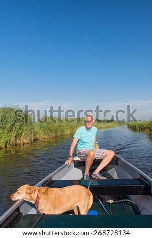 Senior man with dog in motor boat in nature - stock photo