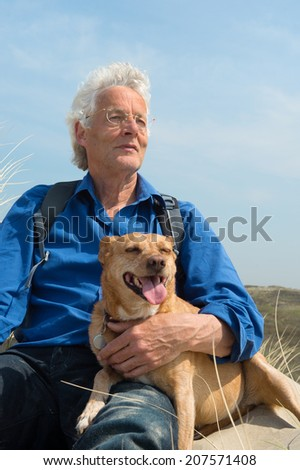 Senior man with dog in nature - stock photo