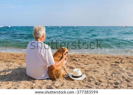 Senior man with dog in white suit sitting at the beach