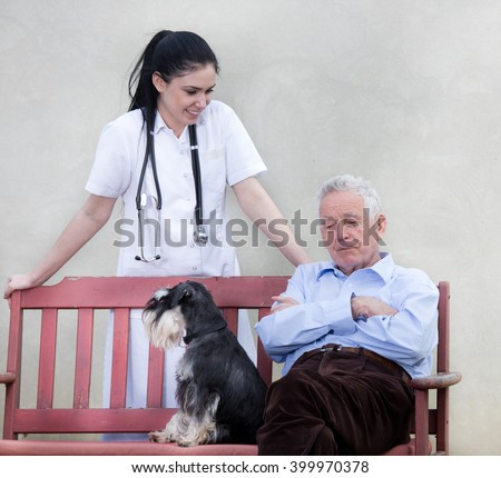 Senior man with dog sitting on the bench while young smiling nurse standing behind him  - stock photo