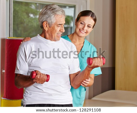 Senior man with dumbbells in rehab with a physiotherapist - stock photo