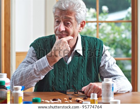 Senior man with glasses on table strokes chin and looks thoughtfully at many pills on table in front of him. Focus on man. Frontal view, green and white color palette. - stock photo