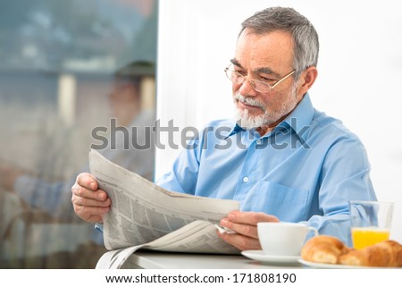 Senior man with glasses reading newspaper at breakfast - stock photo