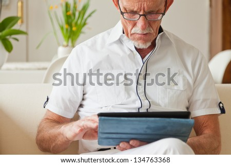 Senior man with glasses using tablet on couch in living room. - stock photo