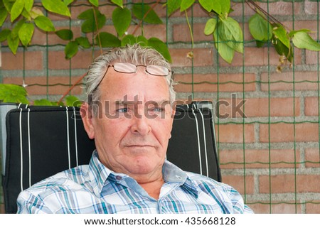 Senior man with grey hair sitting outside in deeps thoughts with reading glasses on his forehead - stock photo