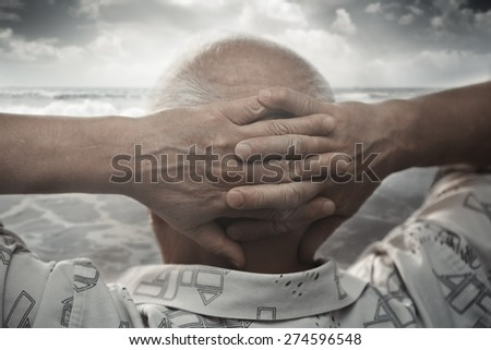 Senior man with hands behind his head looking at the sea - stock photo