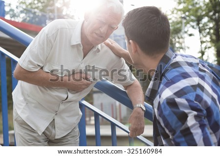 Senior man with heart attack needing first aid - stock photo