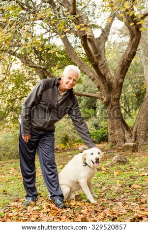 Senior man with his dog in park on an autumns day
