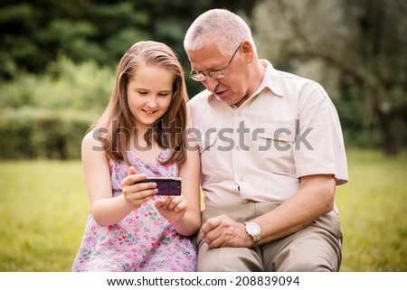 Senior man with his grandchild looking together on photos in smartphone - outdoor in nature - stock photo