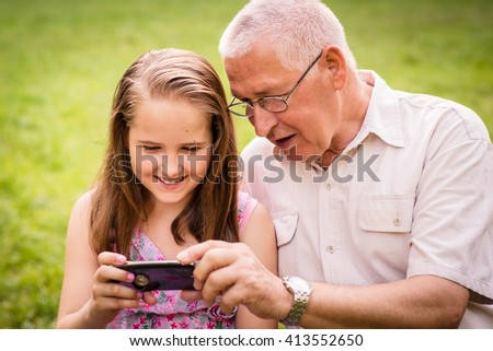 Senior man with his grandchild looking together on photos in smartphone - outdoor in nature