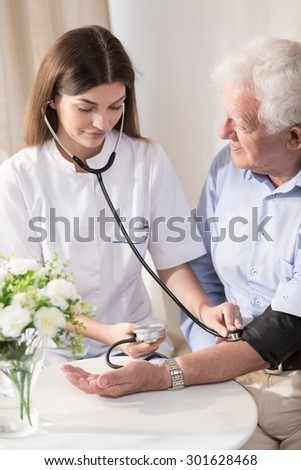Senior man with hypertension having measured blood pressure - stock photo