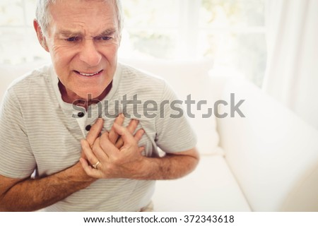 Senior man with pain on heart in bedroom - stock photo