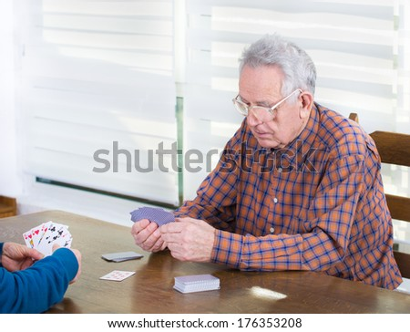 Senior man with reading glasses thinking about next step in card game - stock photo