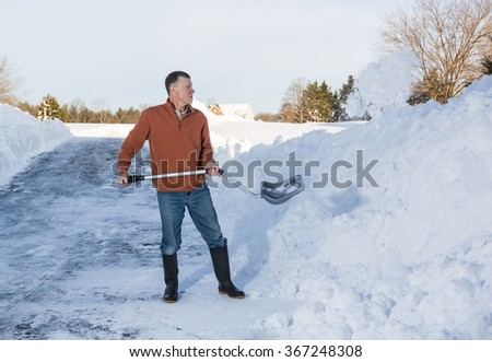 Senior man with snow shovel finishes removing snow drifts on driveway by digging out from the blizzard