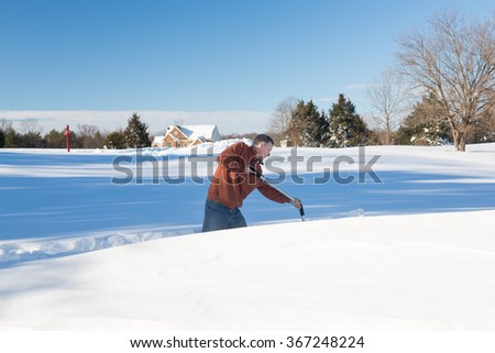 Senior man with snow shovel looking at snow drifts on driveway as he tries to dig out from the blizzard - stock photo