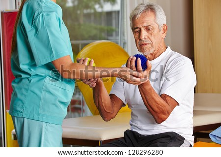 Senior man with spikey balls in gym with physiotherapist - stock photo