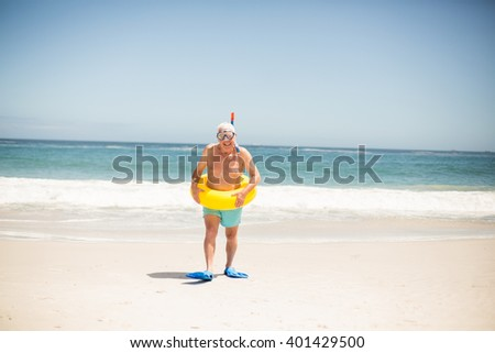 Senior man with swimming ring and flippers at the beach on a sunny day - stock photo
